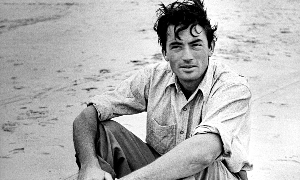 A young Gregory Peck sitting on a sandy beach, trousers rolled up, cigarette in hand